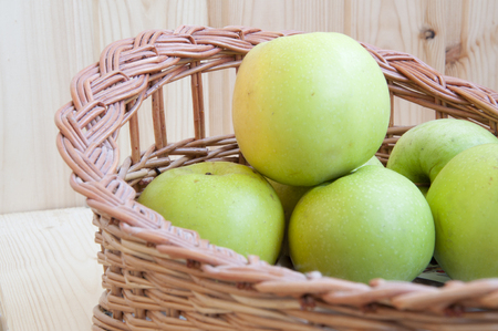 green apples in a basket on the wood background