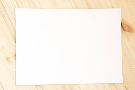 a sheet of white paper on wooden background