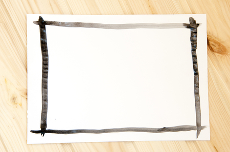 a sheet of white paper with black painted frame on wooden background Zdjęcie Seryjne
