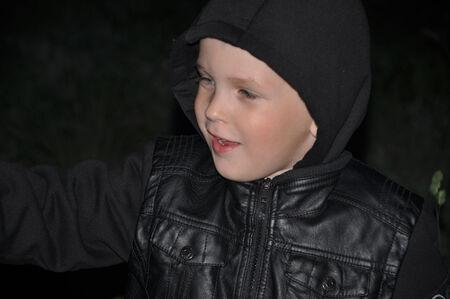 a little boy in a black jacket on a dark background Zdjęcie Seryjne
