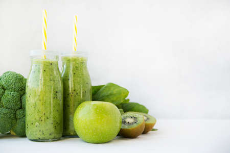 Two glass bottles of healthy green fruit and vegetable smoothie on white background. Detox drink of broccoli, spinach, kiwi and Apple stands on a light table. Horizontal orientation with copy space