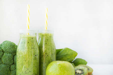 Two glass bottles of healthy green fruit and vegetable smoothie on white background. Detox drink of broccoli, spinach, kiwi and Apple stands on a light table. Horizontal orientation