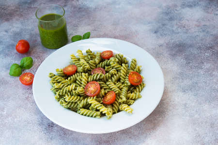 Italian pasta with green sauce Basil pesto, parsley and nuts in a plate on a concrete table. traditional Italian dish.