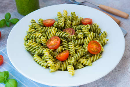 Italian pasta fusilli with green sauce Basil pesto, parsley and nuts in a plate on a concrete table. traditional Italian dish.