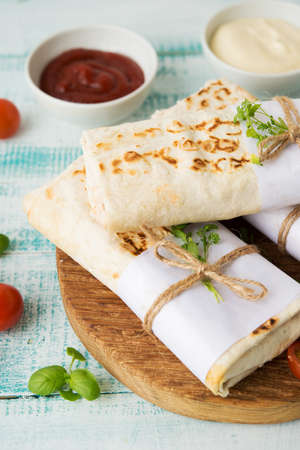 Traditional Mexican food burritos with beans and vegetables. Vegetarian rolls with red beans and vegetables lie on an aged wooden table.