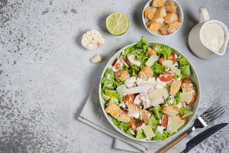 Italian Caesar salad with chicken on gray concrete background