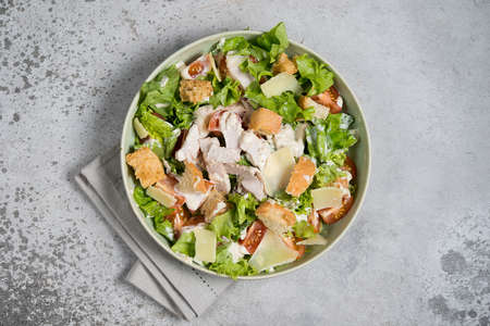 Italian Caesar salad with chicken breast on gray concrete background Фото со стока