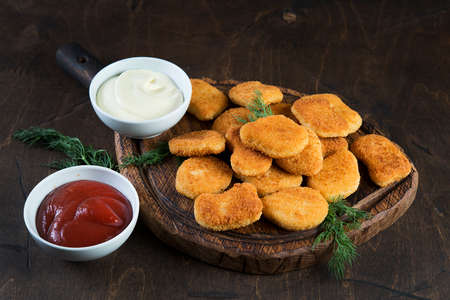 Homemade chicken nuggets with sauce on wooden board on dark background