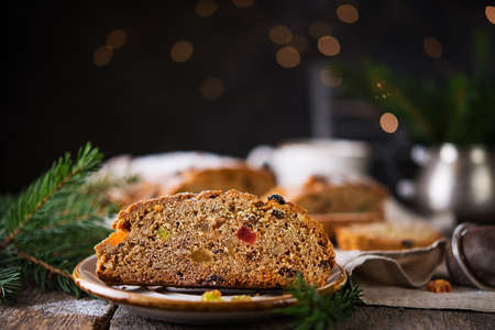 A traditional German Christmas Stollen lies on a wooden table. A celebratory cake is cut into slices with candied fruits, nuts and raisins. Selective focus.