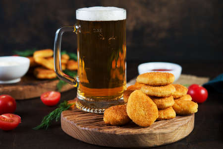 A mug of cold beer with foam with appetizer, chicken nuggets and sauce served on a wooden table.