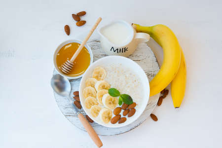 The concept of proper nutrition. Healthy Breakfast of oatmeal with banana, honey and nuts in a white plate in the center of the table on a white background. Horizontal orientation. Top view. Banco de Imagens