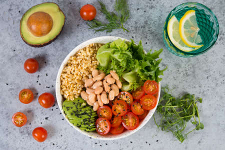 A plate of fresh salad with white beans, bulgur, cherry tomatoes and avocado, decorated with black sesame seeds with products around the plate. Horizontal photo with copy space, top view