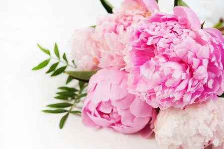 Cerca de ramo de hermosas flores frescas se encuentra sobre un fondo blanco. Las peonías rosas se encuentran a la derecha. Foto horizontal Foto de archivo