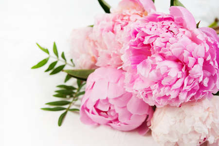 Close up bouquet of fresh beautiful flowers lies on a white background. Pink peonies lie on the right . Horizontal photo Stock Photo