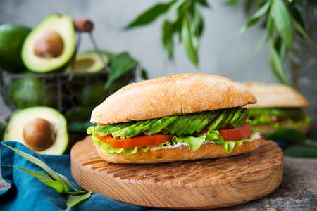 Homemade vegetable sandwich with cream cheese, fresh avocado and tomatoes on a wooden table. Horizontal photo. Selective focus.