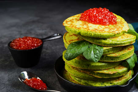 Spinach American pancake stacked in a small pan on a dark background. Horizontal photo.