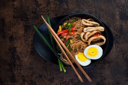 Stir fry with glass noodles, vegetables and seafood in Asian style on a dark wooden background. Horizontal photo. Top view.