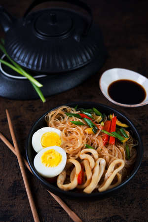 Stir fry with glass noodles, vegetables and seafood in Asian style on a dark wooden background. Vertical photo.