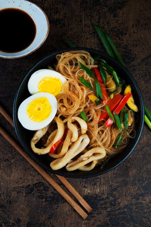 Stir fry with glass noodles, vegetables and seafood in Asian style on a dark wooden background. Vertical photo. Top view.
