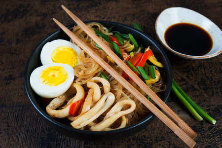 Stir fry with glass noodles, vegetables and seafood in Asian style on a dark wooden background. Horizontal photo.