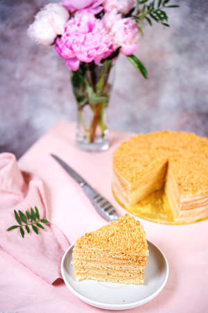 Delicious cake honey cake is on the table with flowers. Banco de Imagens