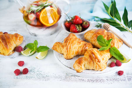 Still life of fresh morning croissants and berry tea in a glass teapot on a white wooden background. Horizontal photo of Breakfast. Foto de archivo - 135501431
