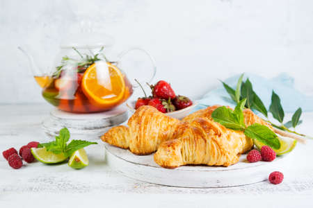 Still life of fresh morning croissants and berry tea in a glass teapot on a white wooden background. Horizontal photo of Breakfast. Foto de archivo - 135501172