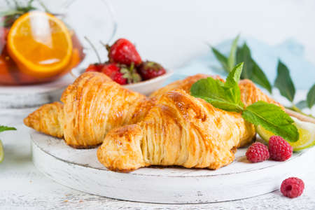 Still life of fresh morning croissants and berry tea in a glass teapot on a white wooden background. Horizontal photo of Breakfast. Close up Foto de archivo - 135501090