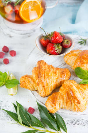 Still life of fresh morning croissants and berry tea in a glass teapot on a white wooden background. Vertical photo of Breakfast. Foto de archivo - 135501155