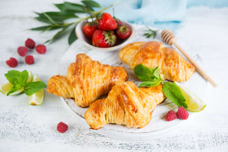 Still life of fresh morning croissants and berry tea in a glass teapot on a white wooden background. Vertical photo of Breakfast. Foto de archivo - 135501183
