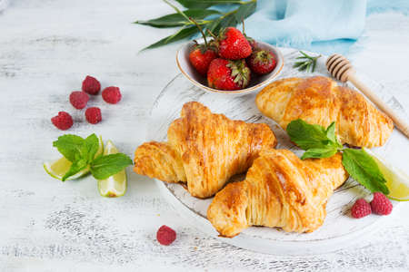 Still life of fresh morning croissants and berry tea in a glass teapot on a white wooden background. Horizontal photo of Breakfast. Foto de archivo - 135501260