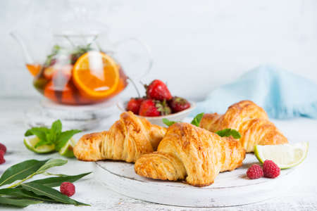 Still life of fresh morning croissants and berry tea in a glass teapot on a white wooden background. Horizontal photo of Breakfast. Foto de archivo - 135501233