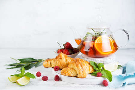 Still life of fresh morning croissants and berry tea in a glass teapot on a white wooden background. Horizontal photo of Breakfast. Foto de archivo - 135501319