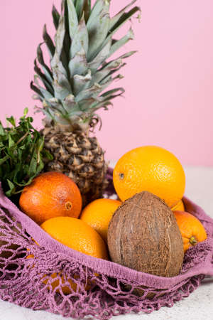 Zero waste shopping, Recycling.The concept of conscious nutrition. A set of products in an eco-friendly bag. Shopping in an eco-friendly style. Fresh fruit in a reusable bag on a pink background. Banco de Imagens