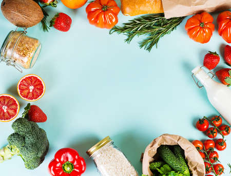 Fruits and vegetables on a blue background, flatlay, top view. The concept of healthy eating. Fresh organic fruits and vegetables are framed on a blue background.