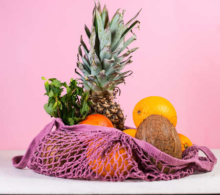 The concept of conscious nutrition. A set of products in an eco-friendly bag. Shopping in an eco-friendly style. Fresh fruit in a reusable bag on a pink background.