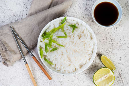 A bowl of cooked rice with chopsticks. Japanese side dish, Top view Stock Photo