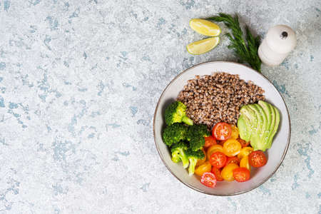 A bowl of cooked buckwheat with vegetables, avocado, tomatoes and broccoli stands on a gray concrete table, vegan food. Top view, close-up, copy space Zdjęcie Seryjne
