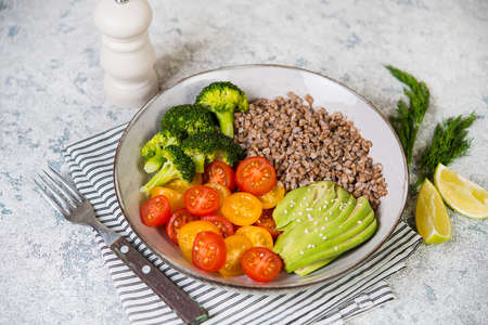 A bowl of cooked buckwheat with vegetables, avocado, tomatoes and broccoli stands on a gray concrete table, vegan food. Top view, close-up, sekective focuse