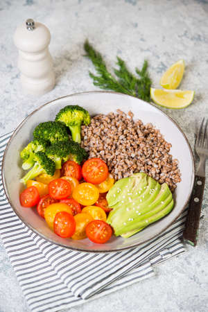 A bowl of cooked buckwheat with vegetables, avocado, tomatoes and broccoli stands on a gray concrete table, vegan food. Top view, close-up