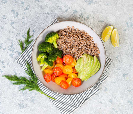 A bowl of cooked buckwheat with vegetables, avocado, tomatoes and broccoli stands on a gray concrete table, vegan food. Top view, close-up Zdjęcie Seryjne