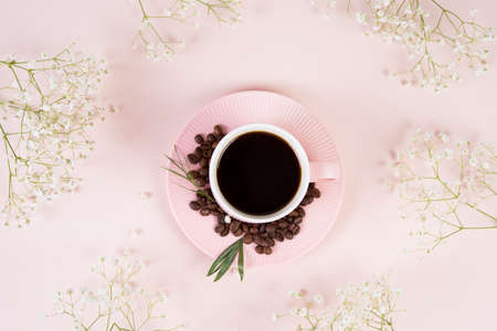 Flat lay with a Cup of black morning coffee surrounded by spring flowers in pastel monochrome tones, top view, spring creative still life