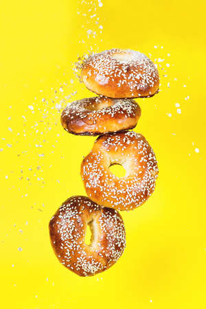 Several bagels in motion fall on a yellow background, a creative image with flying bagels