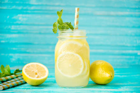 Homemade refreshing lemonade in a jar on a rustic background