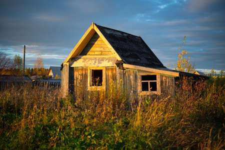 Old wooden village house overgrown with grass, Urals