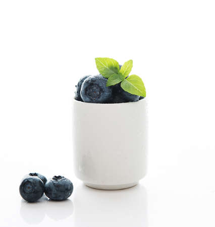 Fresh summer blueberry in a white Cup isolated on a white background 免版税图像