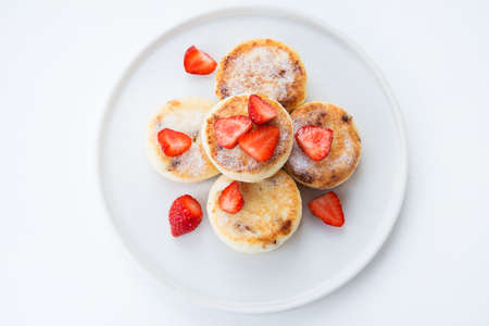 Cottage cheese cheesecakes with strawberries and powdered sugar, top view