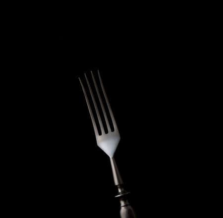 Dining fork isolated on black background with copy space
