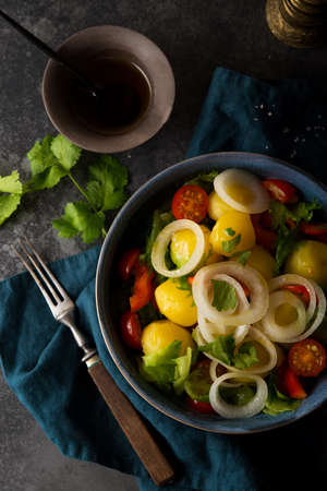 Boiled potatoes with onions and vegetables in a plate, traditional Russian dish, top view