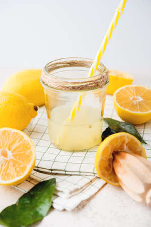 Freshly squeezed natural lemon juice in a glass jar on a white background, selective focus